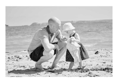 Dad holding daughters hand on the beach